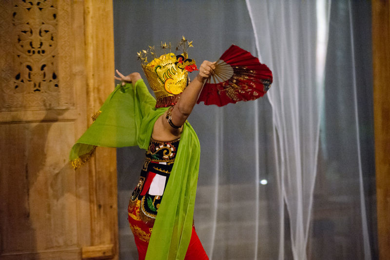 Side View Of Woman In Traditional Clothing Performing Dance By Curtain