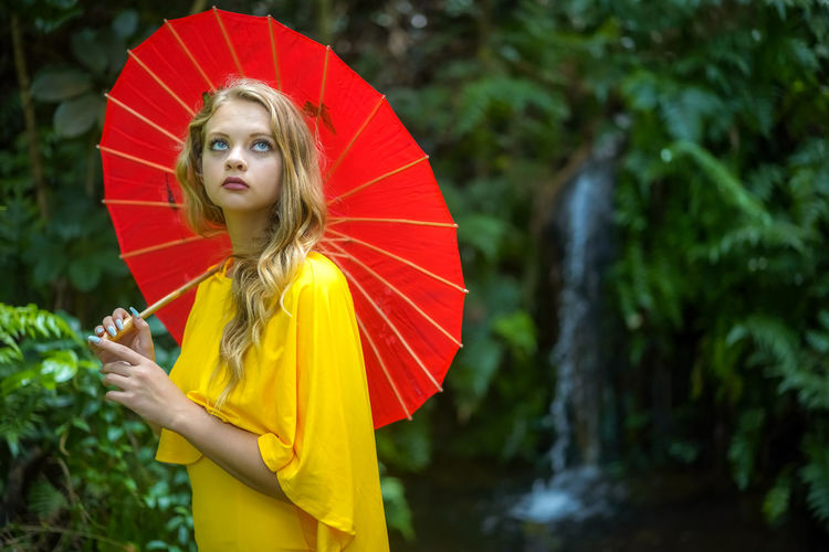 Woman holding red umbrella standing against plants