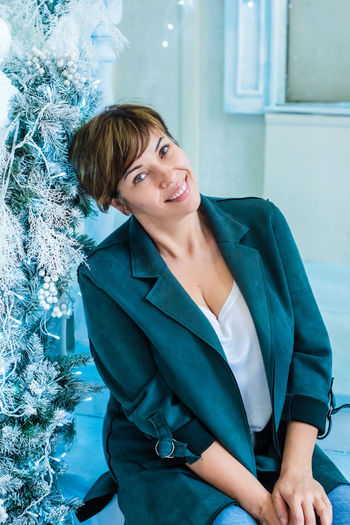 An adult woman is sitting near a christmas tree and smiling. blue and turquoise color. new year