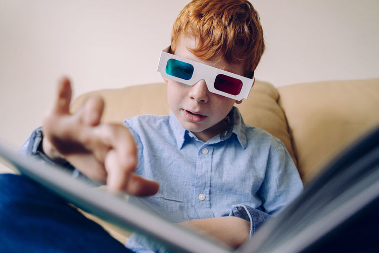 Boy gesturing while wearing 3-d glasses