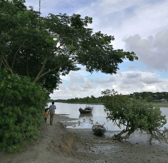 Tree Water Nature River Sky Outdoors Nautical Vessel Scenics Day Beauty In Nature People Walking Walking Around Countryside Country Road Country Life Village Riverside Path Boats A Man And A Child Day Back View Landscape Mud