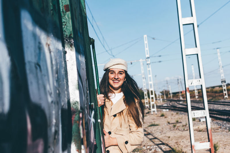 Portrait of smiling young woman standing in train