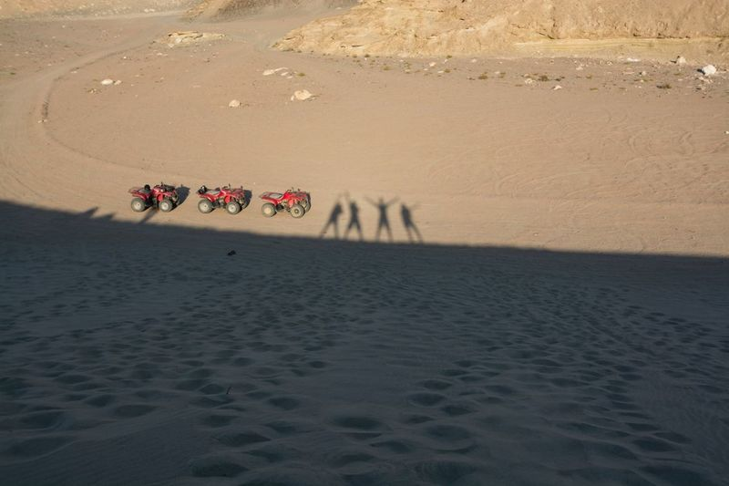 Shadow Of People By Quadbike On Sand In Desert During Sunny Day