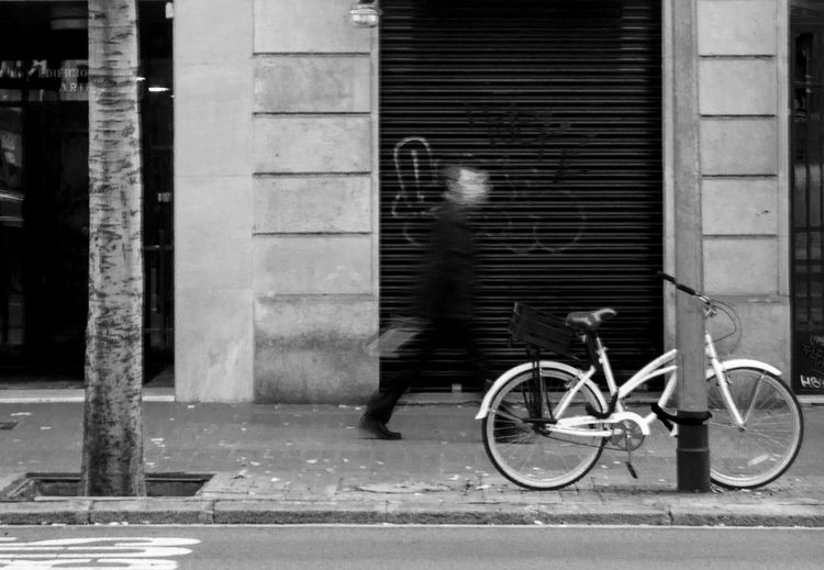 Man riding bicycle on sidewalk in city