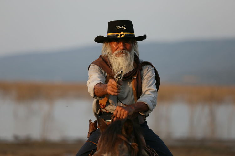 Hat Real People One Person Clothing Focus On Foreground Lifestyles Leisure Activity Front View Men Adult Day Nature Holding Sky Standing Three Quarter Length Gun Senior Adult Cowboy Obscured Face