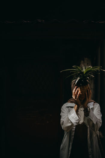 Woman covering face with pineapple standing outdoors at night