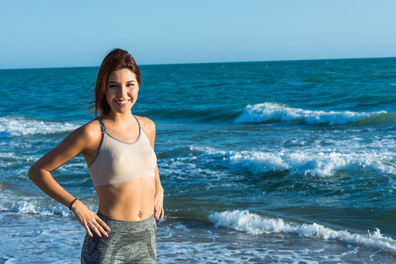 Young Woman Wearing Sports Clothing While Standing Against Sea