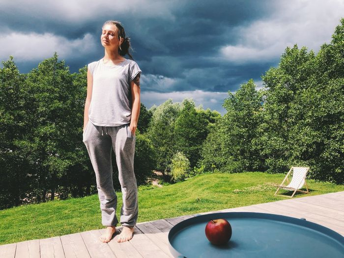 Full length of woman standing by ball against sky