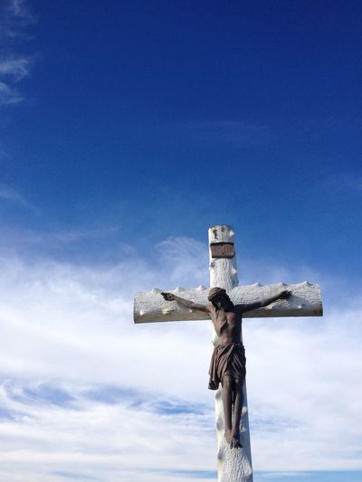 Low angle view of crucifix against blue sky