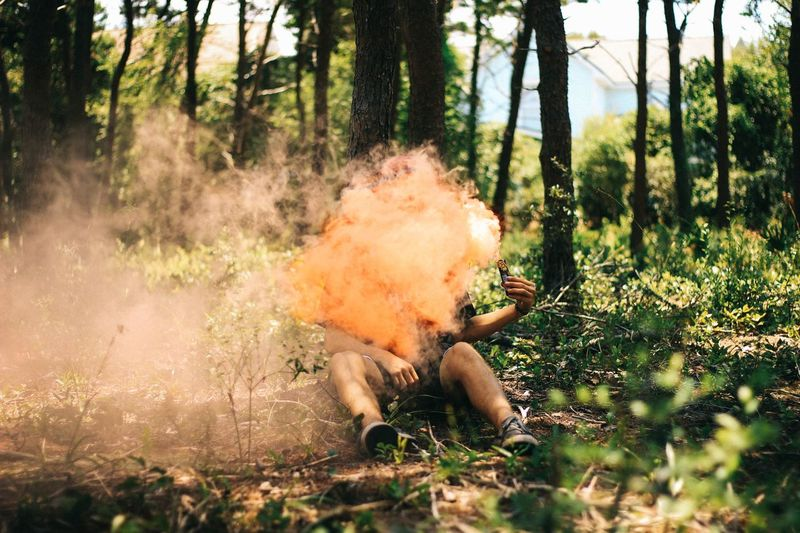 Man with distress flare emitting smoke in forest