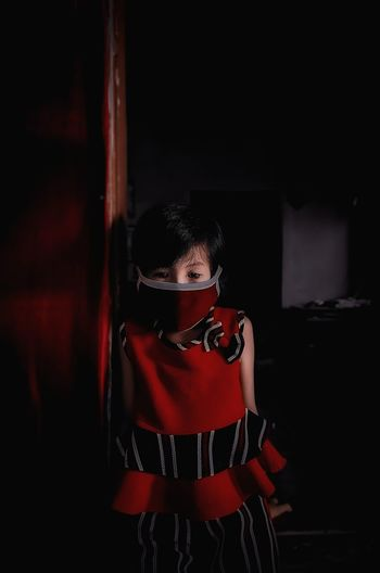 Girl wearing mask while standing at home