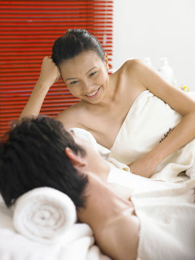 Happy Woman Looking At Boyfriend Relaxing On Bed At Home