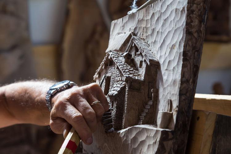 Close-up of craftsperson making sculpture at workshop