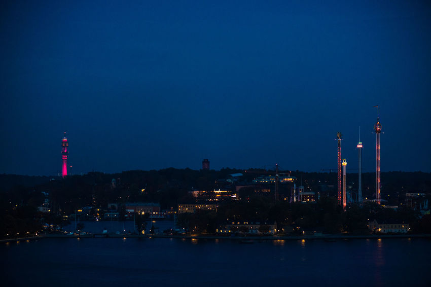 No People Reflection Nature Water Blue Djurgården Building Exterior Built Structure Architecture Illuminated Sky Night Tower Factory Building Waterfront City Smoke Stack Industry Dusk Outdoors Pollution Amusement Park Nightscape Urban Nature