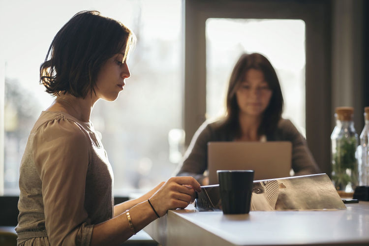Woman sitting on table at cafe