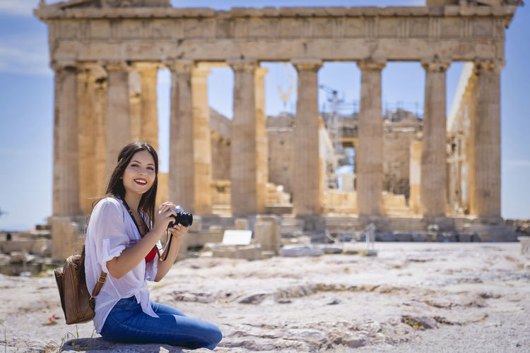 Young woman using mobile phone while sitting on camera