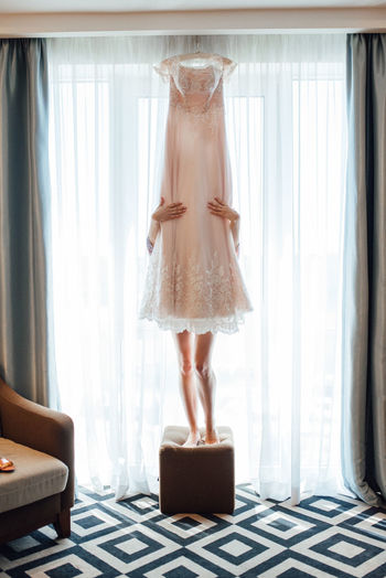Low section of woman standing behind wedding dress indoors
