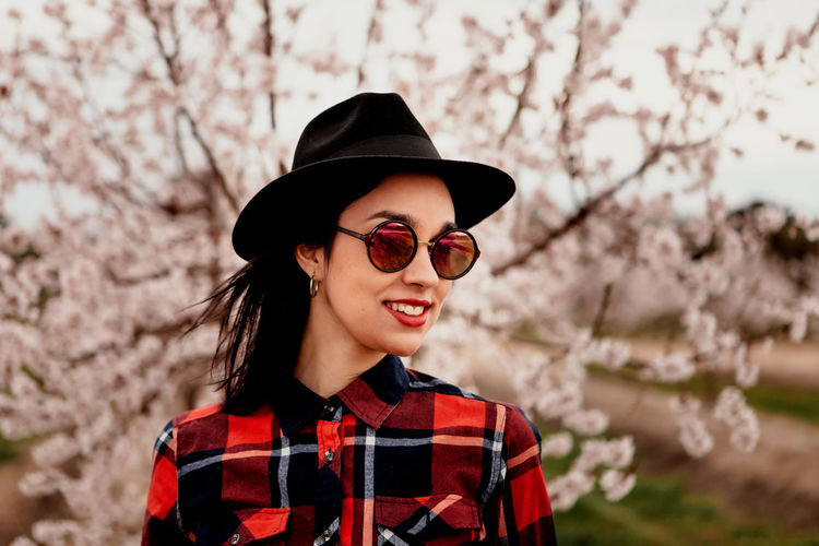 Woman wearing sunglasses and hat against pink flowers