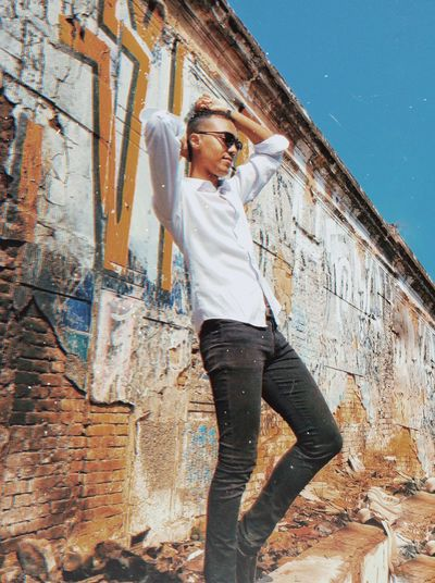 Full length of man standing against graffiti wall