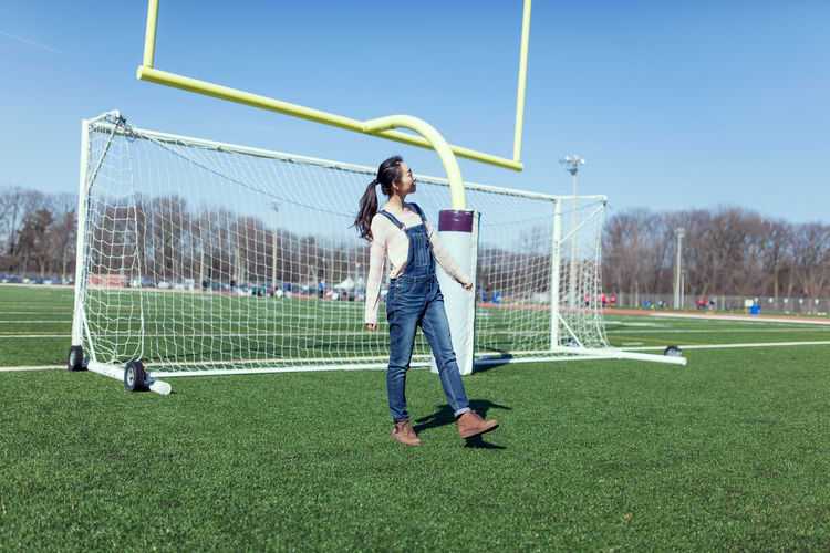 Full length of woman standing on soccer field