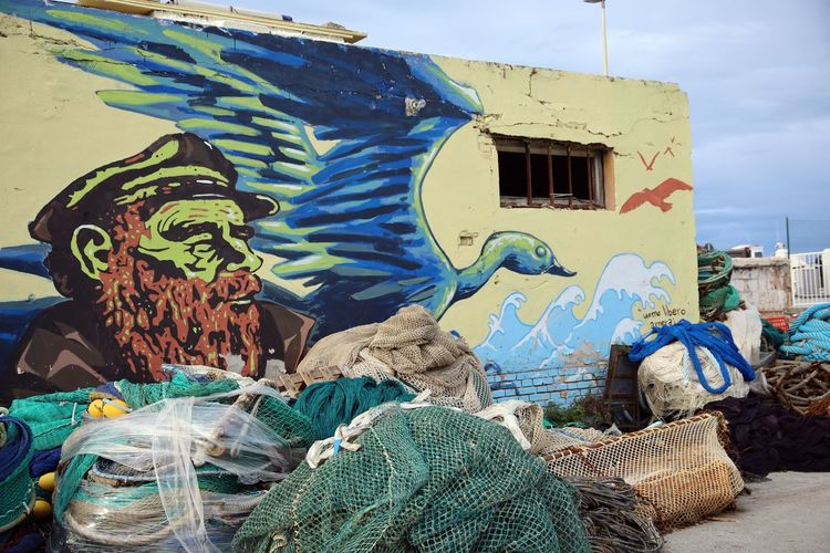 Graffiti on wooden wall and fishing net against sky