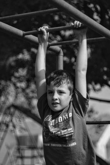 Boy hanging on railing in playground