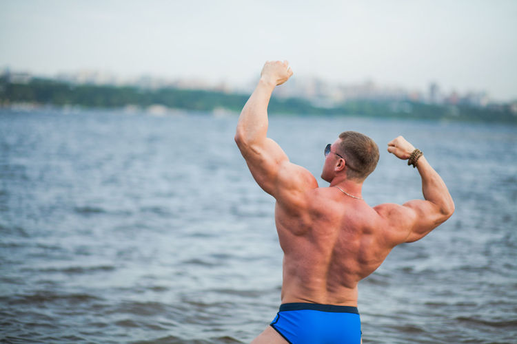 Rear view of shirtless bodybuilder flexing muscles while standing against sea