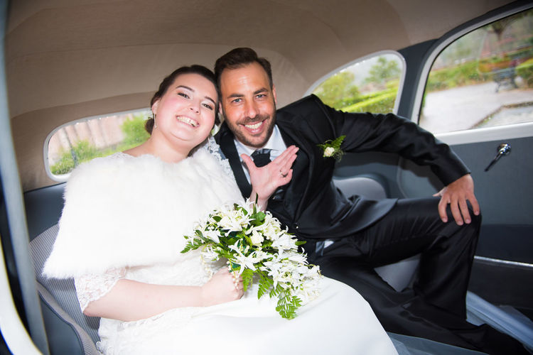 Portrait Of Happy Newly Wed Couple Sitting In Car