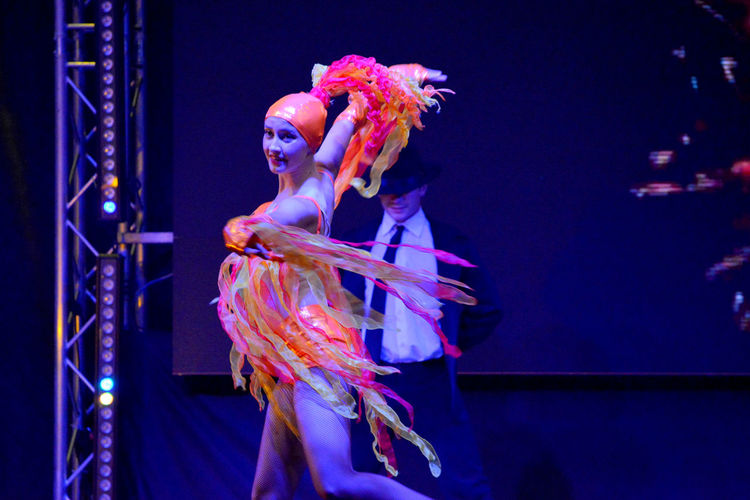 Young woman dancing against illuminated lights at night