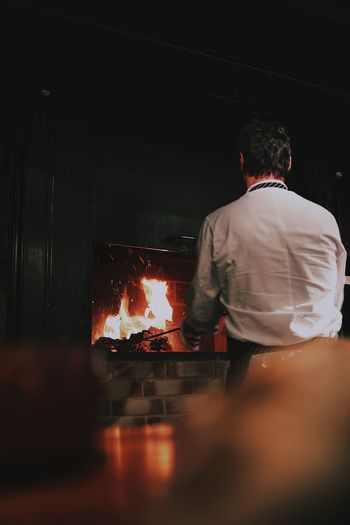 Rear view of chef burning wood in stove