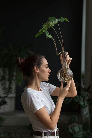 Woman gardener with natural makeup, holding a syngonium in glass flask in her green house