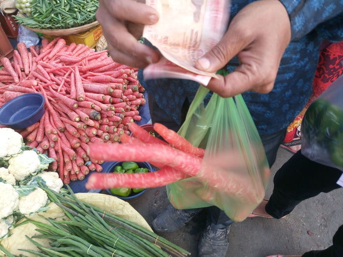 Close-Up Of Man Holding Paper Currency And Carrots In Plastic Bag At Market