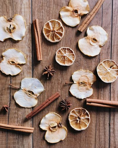 dried apples, oranges and cinnamon on a wooden table Cinnamon Sticks Apple Wooden Table Dried Food Wood - Material Food Indoors  High Angle View Still Life Food And Drink No People Shape Design Healthy Eating Large Group Of Objects Variation Freshness Choice Table Decoration Christmas