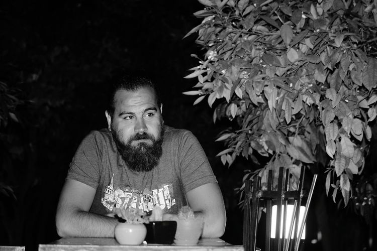 Bearded man sitting at table in restaurant during night