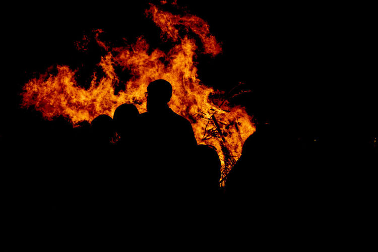Silhouette people with fire at night