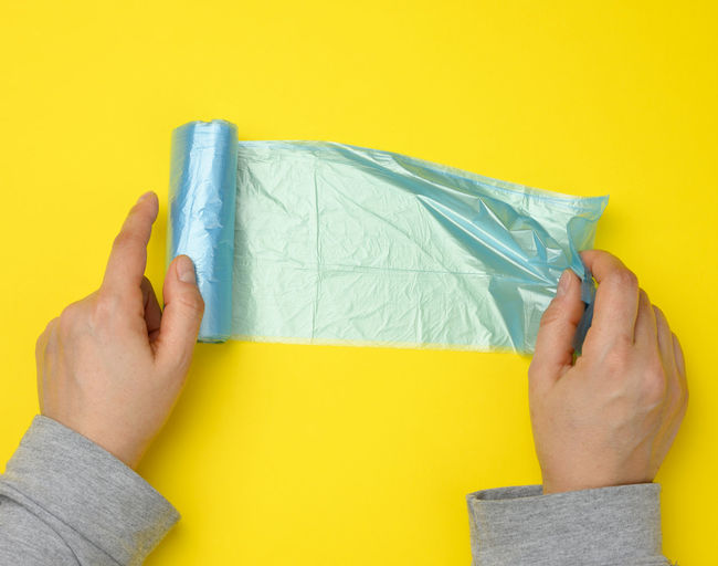 Midsection of person holding paper against yellow wall