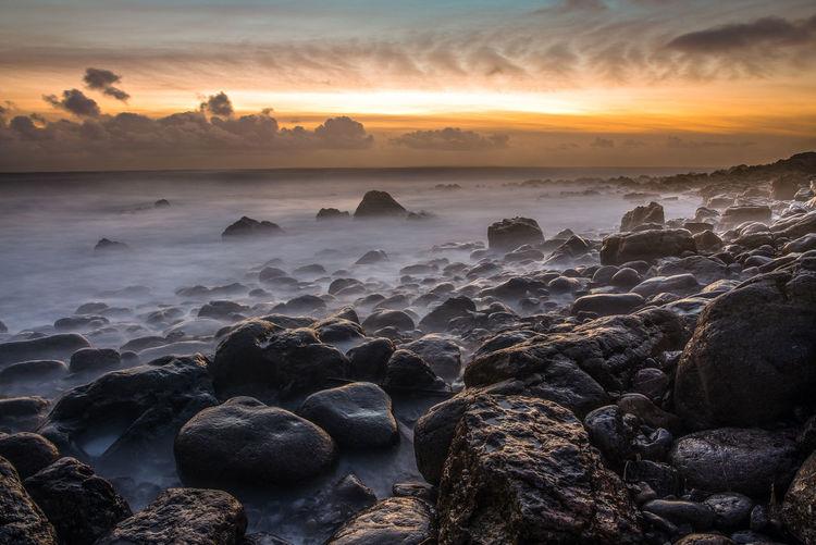 Rocks on shore against sky during sunset