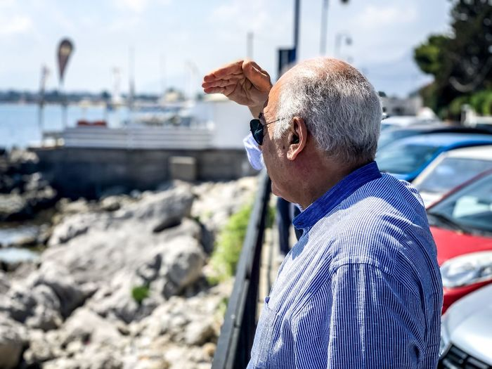 Side view of senior man shielding eyes while standing at beach
