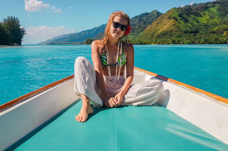 Portrait of woman wearing sunglasses while sitting in boat on sea against mountains and sky
