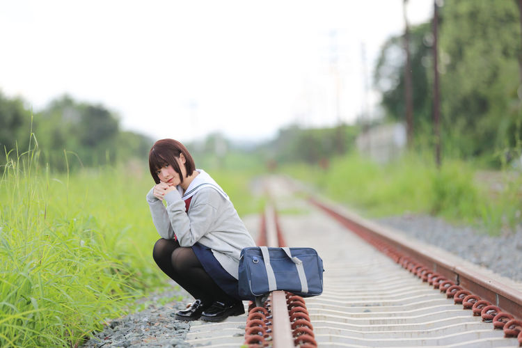 Portrait of woman sitting railroad track