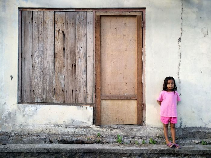 Full Length Of Cute Girl Looking Away While Standing Against House