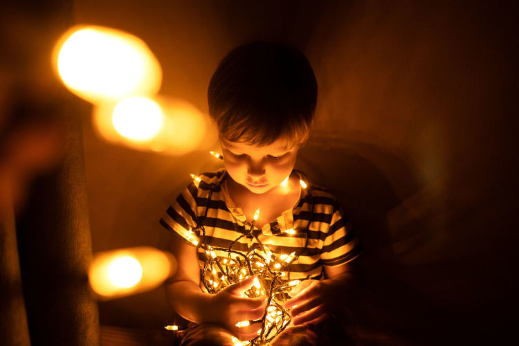 Full length of boy with illuminated lights at home
