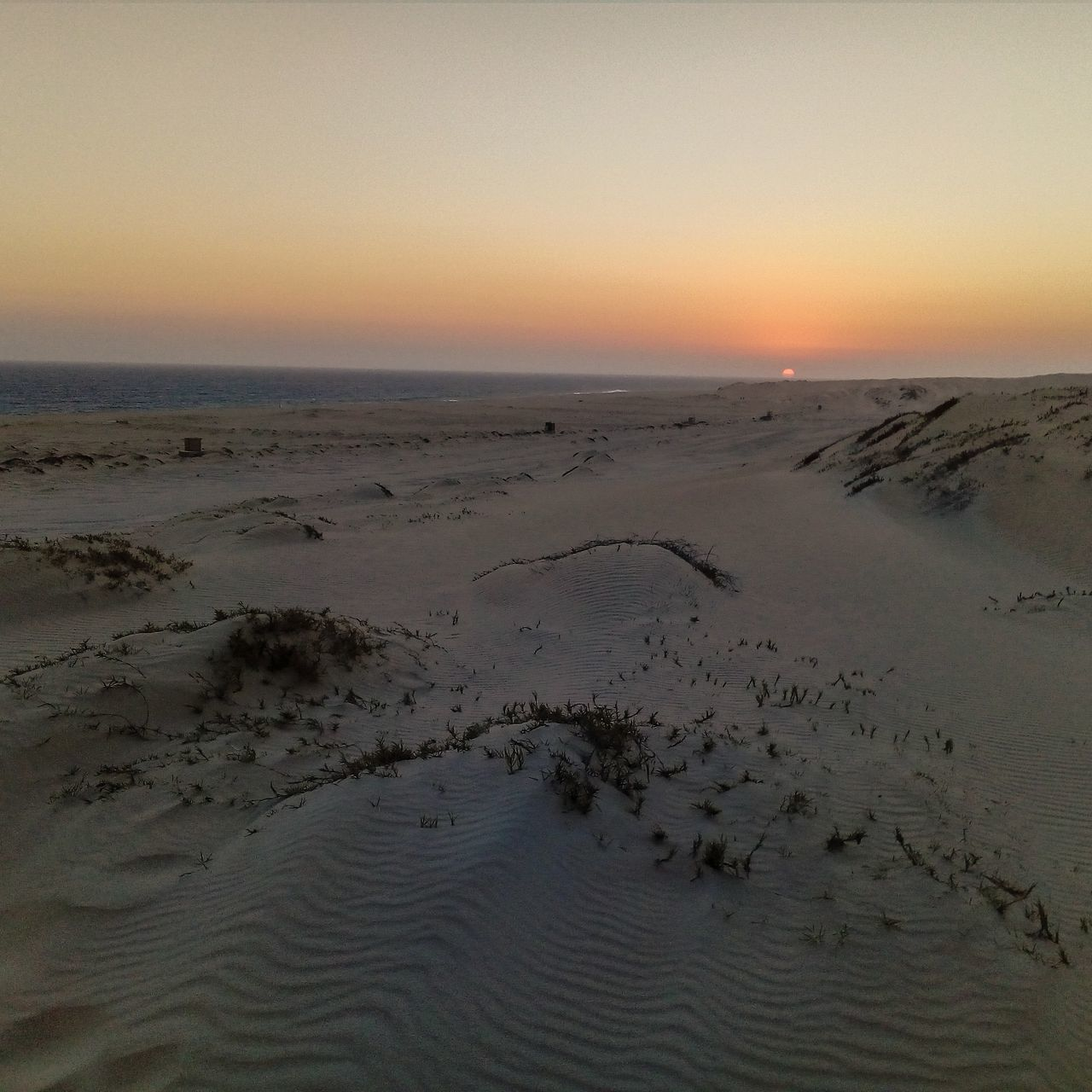 sunset, beauty in nature, nature, sea, scenics, tranquility, tranquil scene, sky, beach, sand, horizon over water, water, outdoors, no people, clear sky, sand dune, day