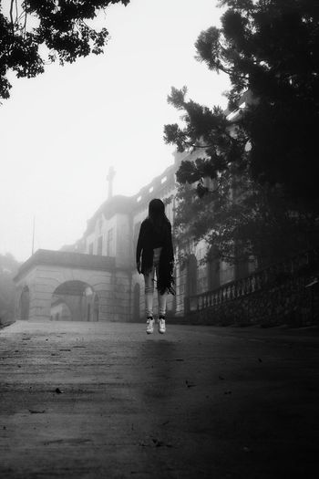 Woman levitating on road leading towards church in foggy weather