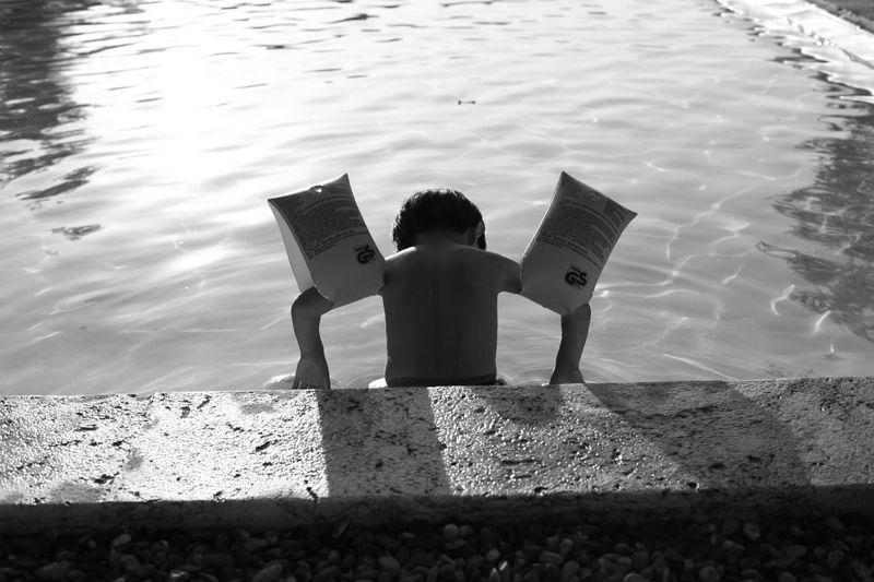 Rear View Of Boy Wearing Water Wings In Lake