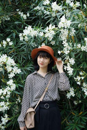 Portrait of beautiful woman standing against plants