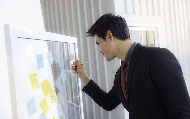 Businessman writing on glass at office
