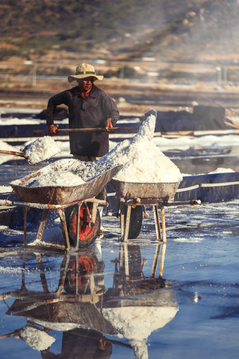 The daily activities in a salt village in Vietnam. Real People One Person Men Water Nature Day Cold Temperature Winter Occupation Front View Holding Adult Clothing Sitting Working Full Length Hat Sunlight Reflection Hard Movement Activity Salt