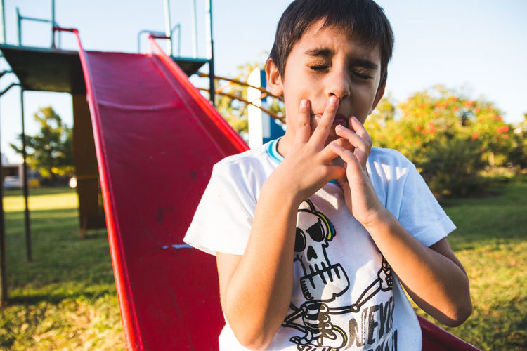 Cute boy gesturing while sitting on slide with eyes closed at playground