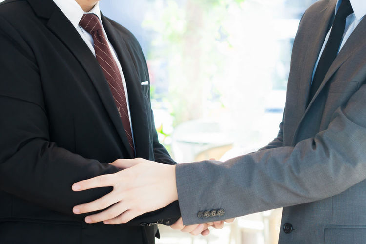 Midsection Of Colleagues Shaking Hands In City